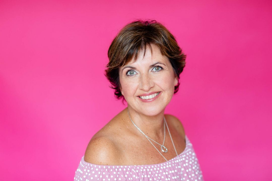 headshot of woman against bright pink background