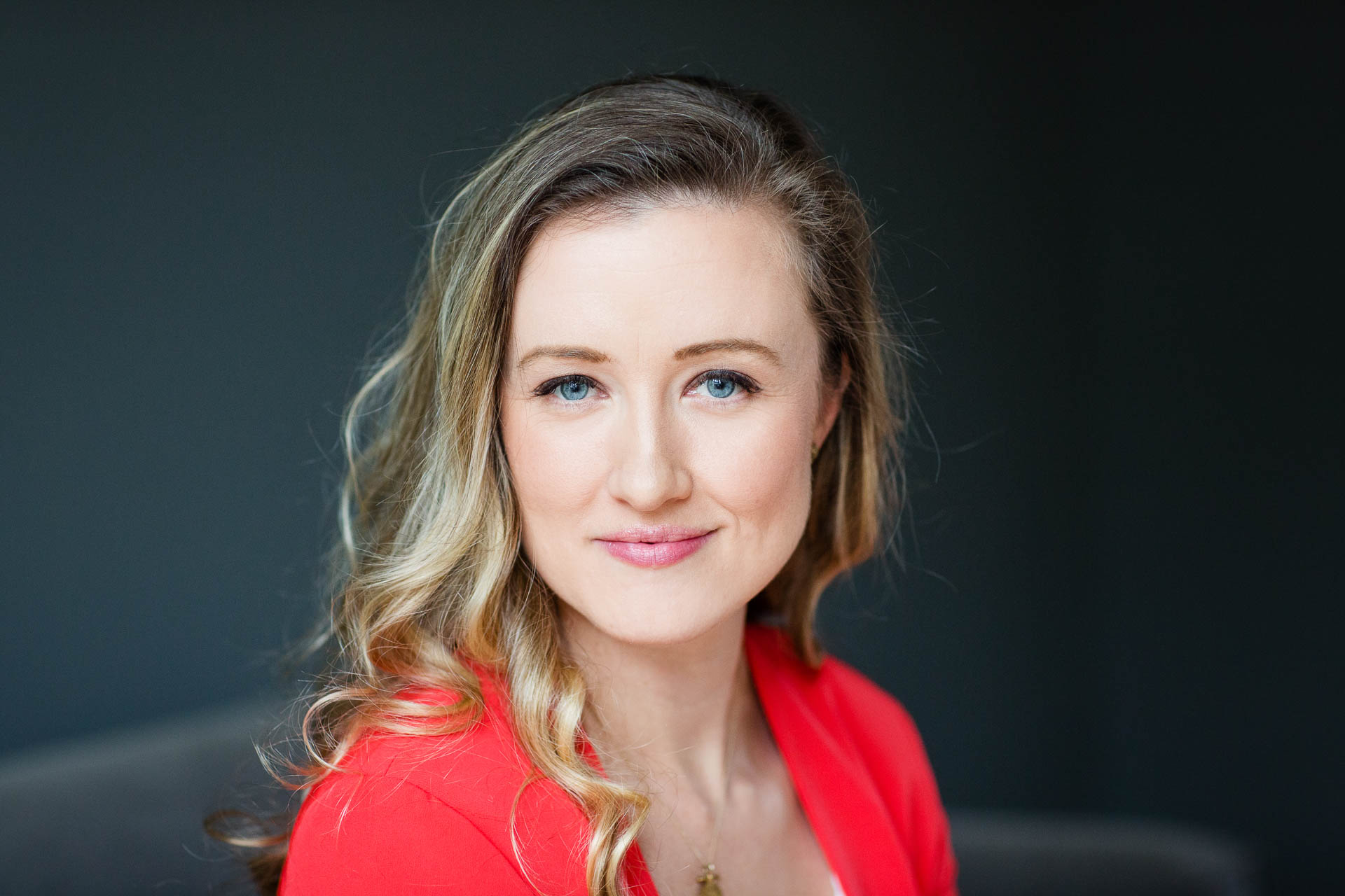headshots or personal brand photography? portrait of woman in red jacket
