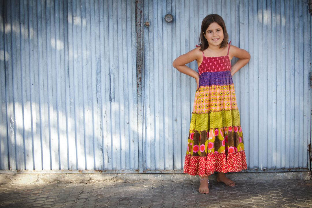 girl in sundress against blue corrugated wall