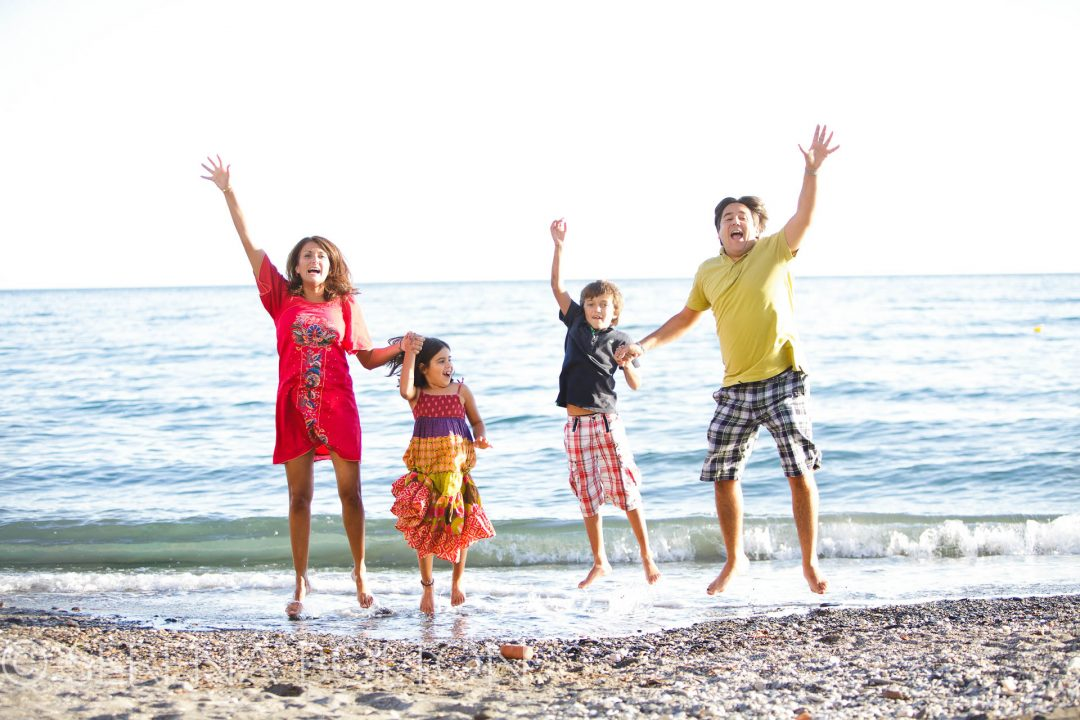 holiday photography of family on beach jumping