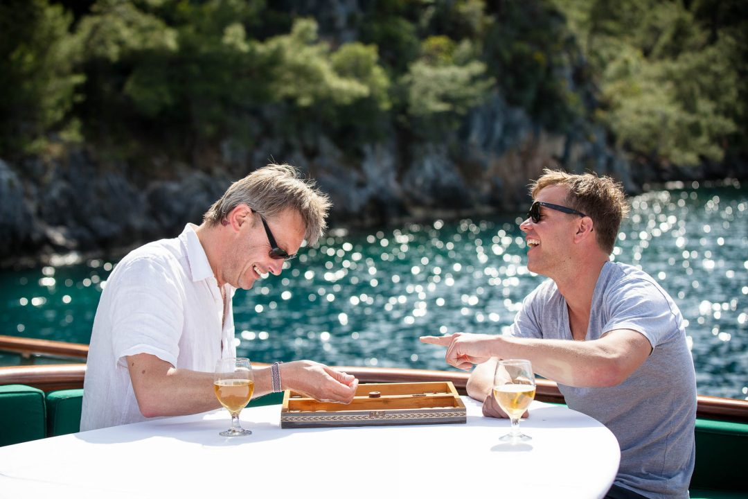 men on holiday playing backgammon on boat